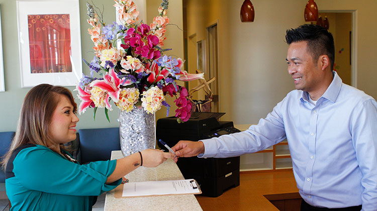 Happy dental patient paying with dental plan