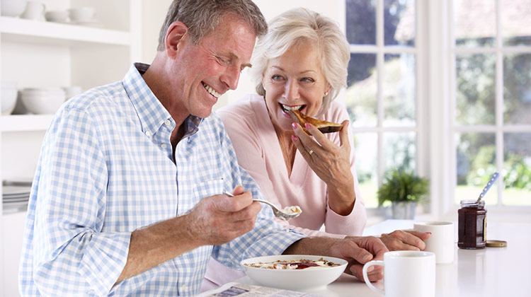 Older couple smiling in kitchen