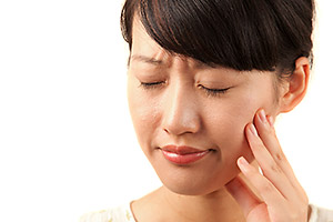 Picture of woman holding her jaw in pain